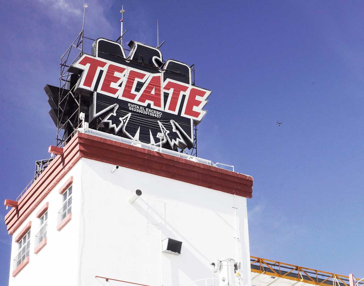 View from below a tower that has the Tecate® logo eagle on top.