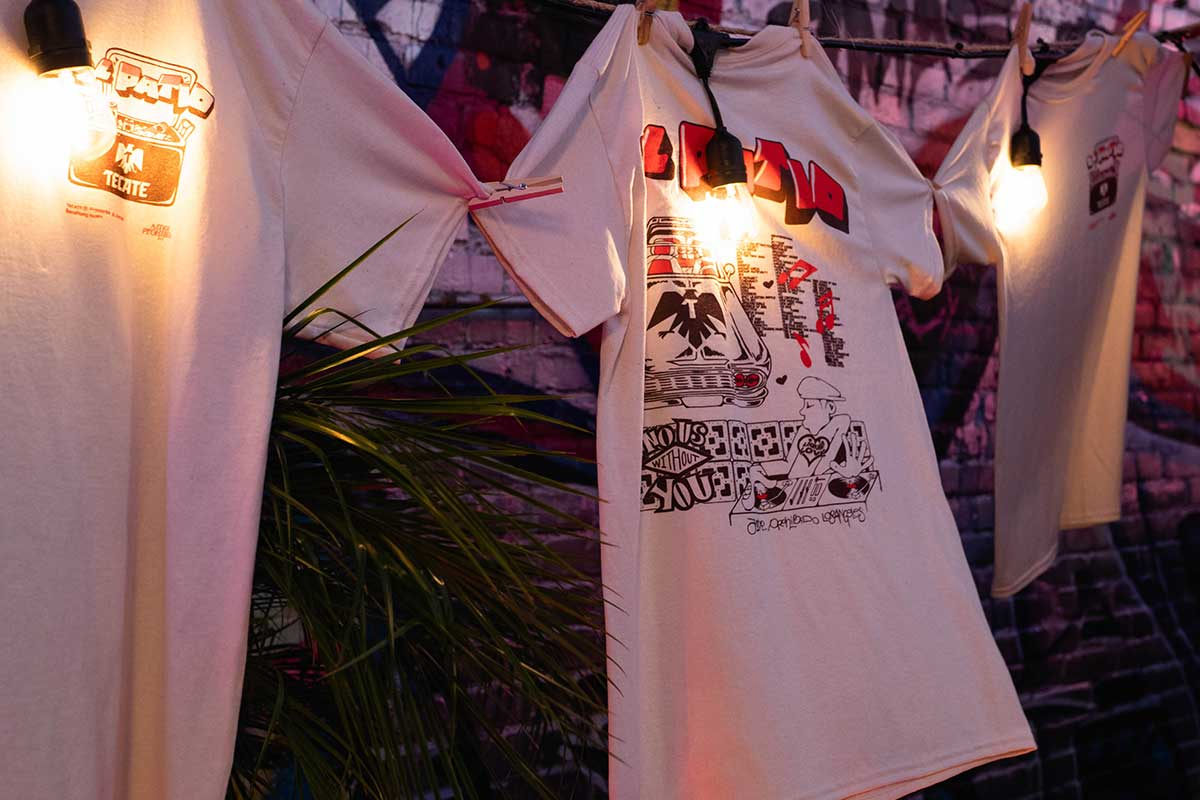 Three T-shirts hanging on a clothesline, designed by Amor Prohibido LA. Merch colaboration.