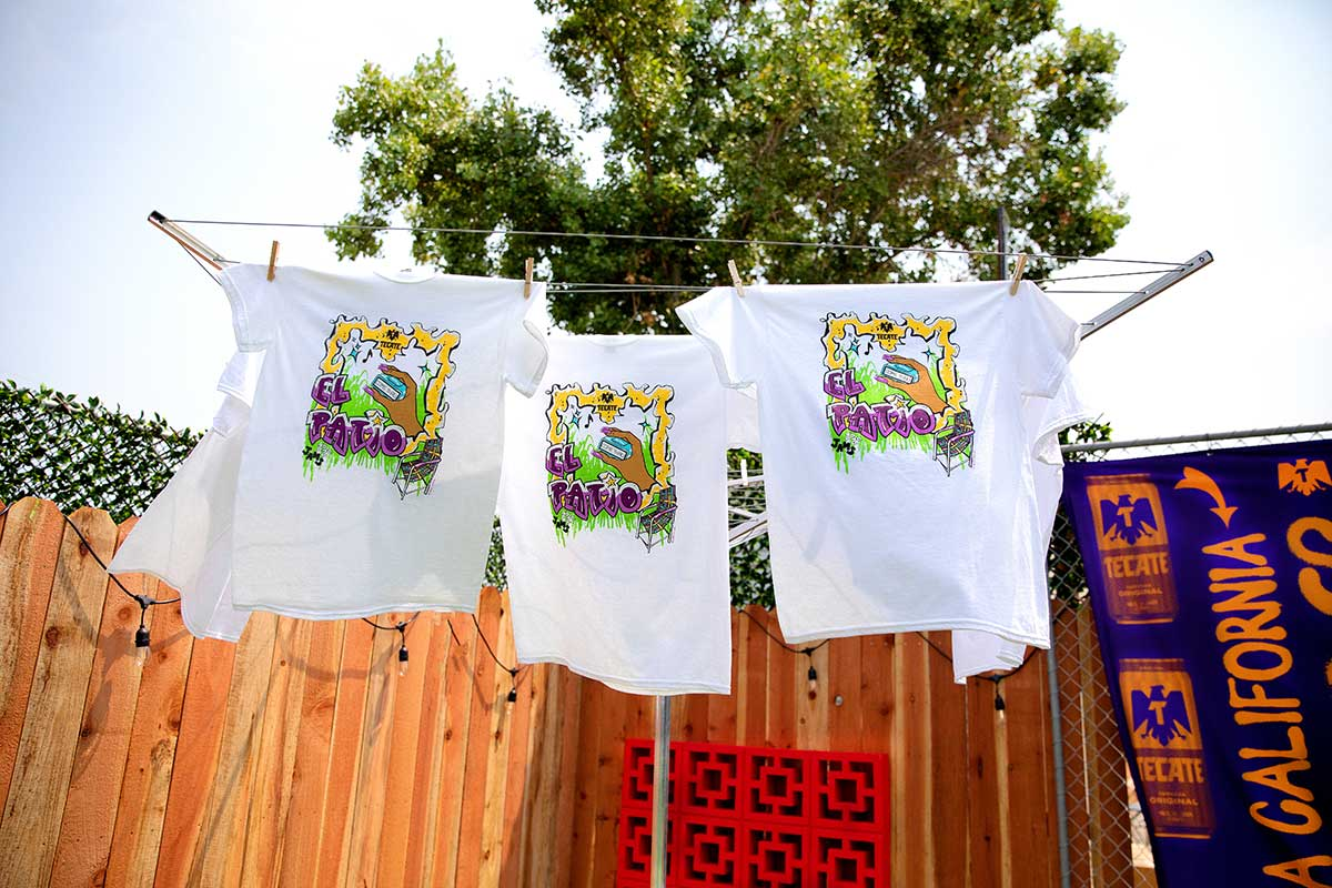 Three El Patio Tecate T-shirts designed by Brenda Equihua hanging on a clothesline