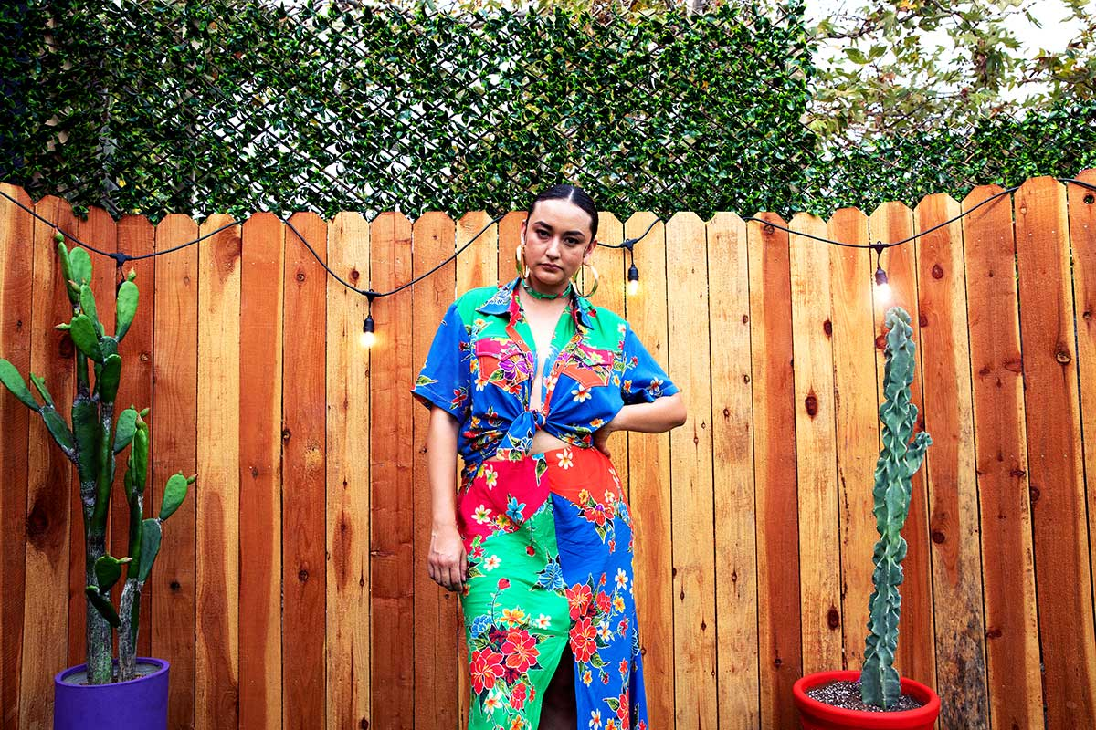 Brenda Equihua poses with a dress standing between two plants