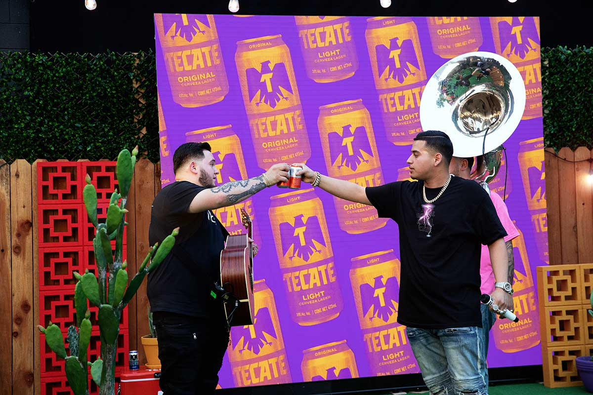 The vocalist and the guitarist of Fuerza Regida cheers with Tecate® Original